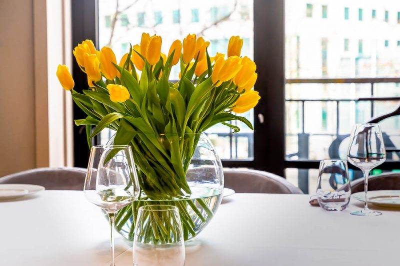 A bouquet of yellow tulips stands in a vase on a table with a white tablecloth.